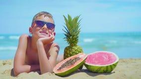 O menino de sorriso encontra-se no litoral com uma composição de frutos exóticos contra o mar filme