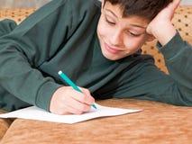 O menino de sorriso escreve uma letra Fotos de Stock