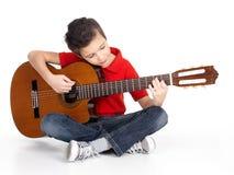 O menino de sorriso está jogando a guitarra acústica Fotos de Stock Royalty Free