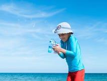 O menino de sorriso feliz o europeu em um t-shirt protetor azul e em um short vermelho do F na praia pelo mar azul começa acima b foto de stock royalty free