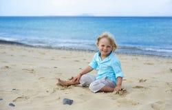 O menino de sorriso pequeno bonito joga na praia Foto de Stock