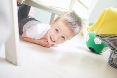 O menino de sorriso pequeno está encontrando-se em um assoalho em casa fotos de stock