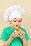 O menino de sorriso pequeno no chapéu dos cozinheiros chefe come a pizza cozinhada Fotografia de Stock Royalty Free