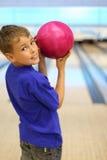 O menino de sorriso prende a esfera no clube do bowling Imagens de Stock Royalty Free