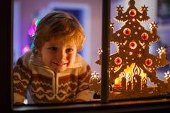 O menino de sorriso que está pela janela no tempo do Natal e que guarda pode Imagens de Stock Royalty Free