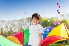 O menino de sorriso que joga o arco-íris salta de paraquedas no parque Fotografia de Stock