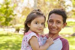 O menino de sorriso que leva sua irmã mais nova olha à câmera Imagem de Stock