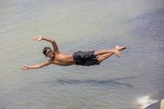 O menino desabrigado é jogo de salto em áreas de Sadarghat do rio de Karnafuli, Chittagong do divertimento, Bangladesh Foto de Stock
