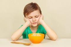 O menino desagradado pequeno não quer comer o cereal fotografia de stock