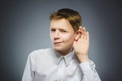 O menino desapontado escuta audição da criança algo, mão ao gesto da orelha fotos de stock