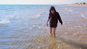 O menino descalço da criança anda na praia da areia na água fria do mar em férias filme