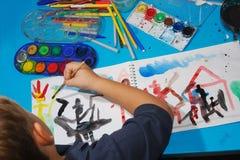 O menino desenha um retrato Fotos de Stock Royalty Free