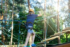O menino desportivo, novo, bonito na camisa branca de t passa seu tempo no parque da corda da aventura no capacete e no equipamen imagem de stock