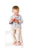 O menino disparou no estúdio em um assento de sorriso do fundo branco Fotografia de Stock