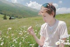O menino do adolescente que examina o gafanhoto verde em montanhas alpinas ajardina o fundo Fotos de Stock