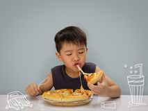 O menino do ano do asiático 6-7 está feliz a comer a pizza com os wi quentes de um queijo foto de stock