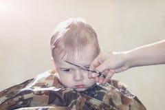 O menino do bebê de um ano faz pela primeira vez o corte de cabelo em uma barbearia Fotos de Stock Royalty Free