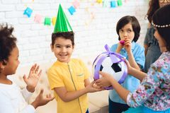 O menino do feliz aniversario recebe a bola do futebol como o presente de aniversário Festa de anos feliz Foto de Stock