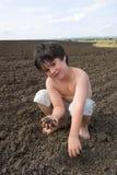 O menino do liitle com terra preta fotografia de stock