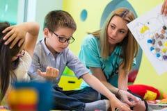 O menino do pré-escolar que aprende ler ajudou por um kindergart dedicado fotografia de stock