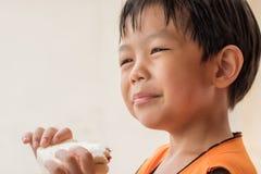 O menino do sorriso está comendo o pão de forma imagens de stock royalty free