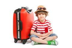 O menino do verão senta-se no tronco vermelho Imagem de Stock