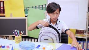 O menino dobra livros de texto e os cadernos em uma escola backpack video estoque