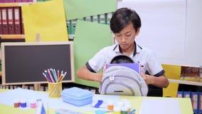 O menino dobra livros de texto e os cadernos em uma escola backpack vídeos de arquivo
