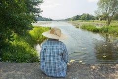 O menino dobrando com a vara de pesca na ponte concreta suporta a vista imagens de stock royalty free