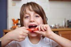 o menino dos anos de idade 6 come o tomate cortado Fotos de Stock Royalty Free