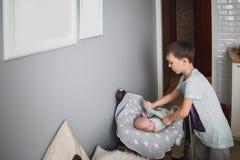 O menino dos anos de idade 8 cobre com cuidado sua irmã recém-nascida com uma cobertura Imagens de Stock Royalty Free
