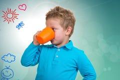 O menino dos anos de idade 3 em pontos azuis bebe de uma caneca Fotos de Stock Royalty Free
