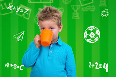 O menino dos anos de idade 3 em pontos azuis bebe de uma caneca Imagem de Stock