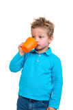 O menino dos anos de idade 3 em pontos azuis bebe de uma caneca, isolada no branco Foto de Stock