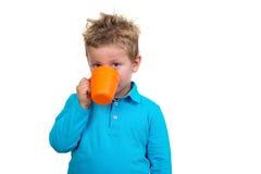 O menino dos anos de idade 3 em pontos azuis bebe de uma caneca, isolada no branco Fotografia de Stock Royalty Free