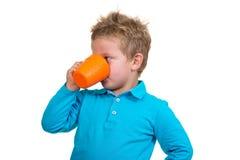 O menino dos anos de idade 3 em pontos azuis bebe de uma caneca, isolada no branco Imagens de Stock Royalty Free