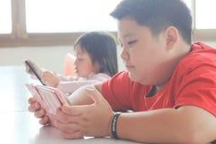 O menino e as meninas asiáticos da criança são aditivos jogando a tabuleta e os telefones celulares Fotografia de Stock