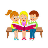 O menino e as meninas no banco leram o livro Imagens de Stock Royalty Free