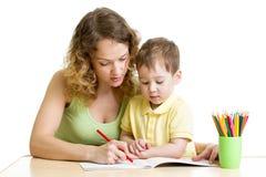 O menino e a mãe da criança tiram com lápis coloridos Imagem de Stock