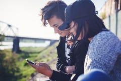 O menino e a menina adolescentes asiáticos olham no smartphone, comunicam, têm o fu Foto de Stock Royalty Free