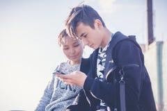 O menino e a menina adolescentes asiáticos olham no smartphone, comunicam, têm o fu Imagens de Stock