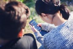 O menino e a menina adolescentes asiáticos olham no smartphone, comunicam, têm o fu Fotografia de Stock