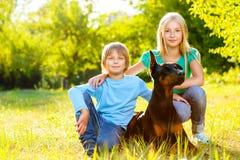 O menino e a menina adoráveis no verão estacionam com seu Imagem de Stock