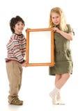 O menino e a menina com um frame foto de stock