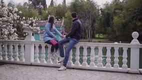 O menino e a menina de amor estão sentando-se em uma cerca de pedra branca sob uma magnólia de florescência perto da água e no ol video estoque
