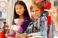 O menino e a menina de sorriso bebem o café dos copos brancos Fotografia de Stock Royalty Free