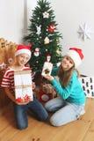 O menino e a menina de sorriso com presentes aproximam a árvore de Natal Imagem de Stock