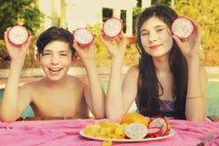 O menino e a menina do adolescente dos irmãos com corte do dracon frutificam Fotografia de Stock
