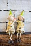 O menino e a menina do sorriso emplastram a boneca na tabela de madeira Fotografia de Stock Royalty Free