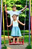 O menino e a menina em um balanço Foto de Stock